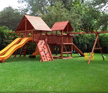 A large Woodplay playset in Coral Springs, Florida, with rock wall, two slides, swingset and wood roofs.