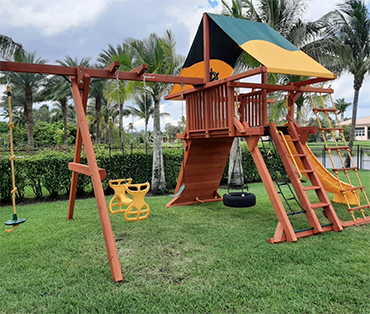 Woodplay angle base with tire swing, rope ladder,climbing wall installed in Davie, Florida.