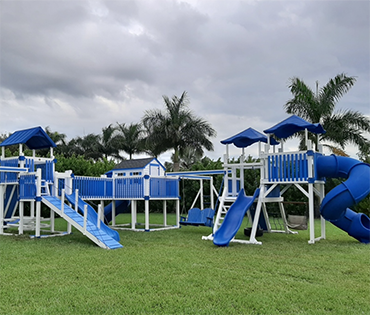 Large Swing Kingdom vinyl playset in Plantation, Florida, installed by Play King.
